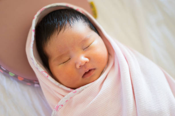 lovely asian infant  sleeping on round little bed, top view,selective focus stock photo