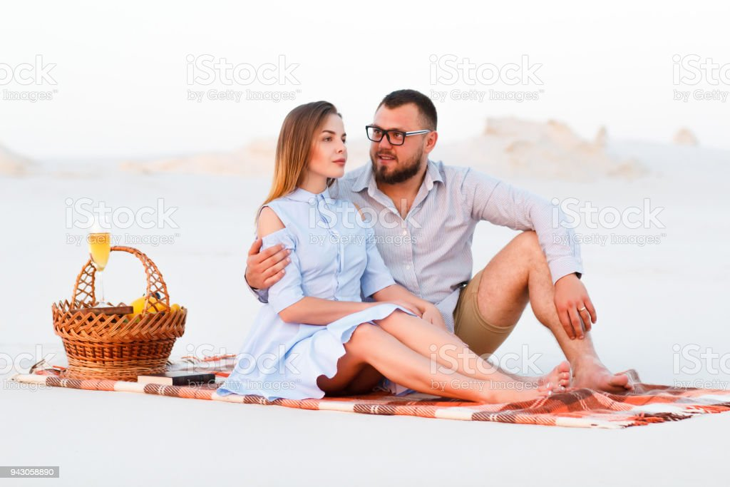 lovely attractive couple sitting together on the white sand beach, happy couple sitting on a blanket , happy couple enjoying picnic on the beach and have good time on summer vacations stock photo