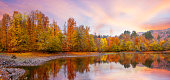 Panoramic photo of a lovely autumn sunset with amazing colours of forest and a perfect sunset skyline reflected on the lake
