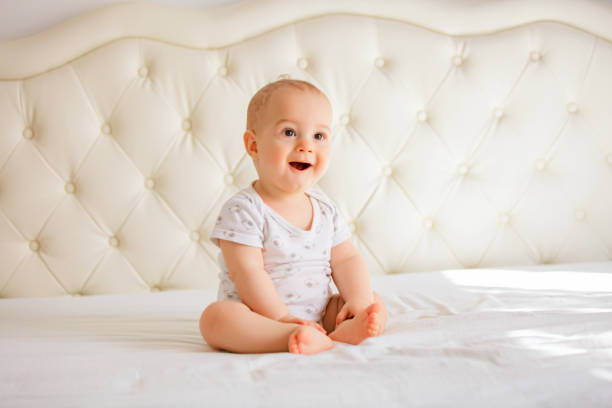 lovely baby boy in white sunny bedroom stock photo