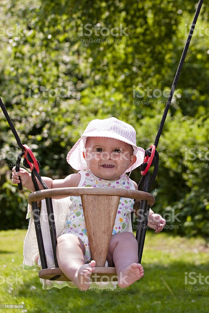 Lovely baby girl sitting in a swing royalty-free stock photo