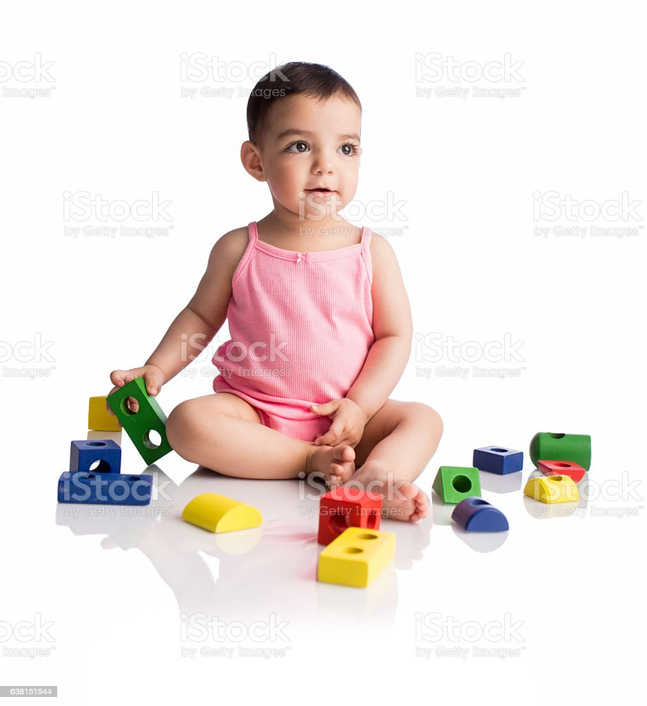 Lovely baby girl sitting with toys and smiling - foto de stock