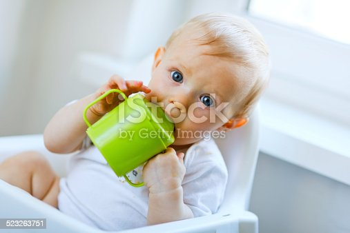 istock Lovely baby  sitting in chair and drinking from cup 523263751