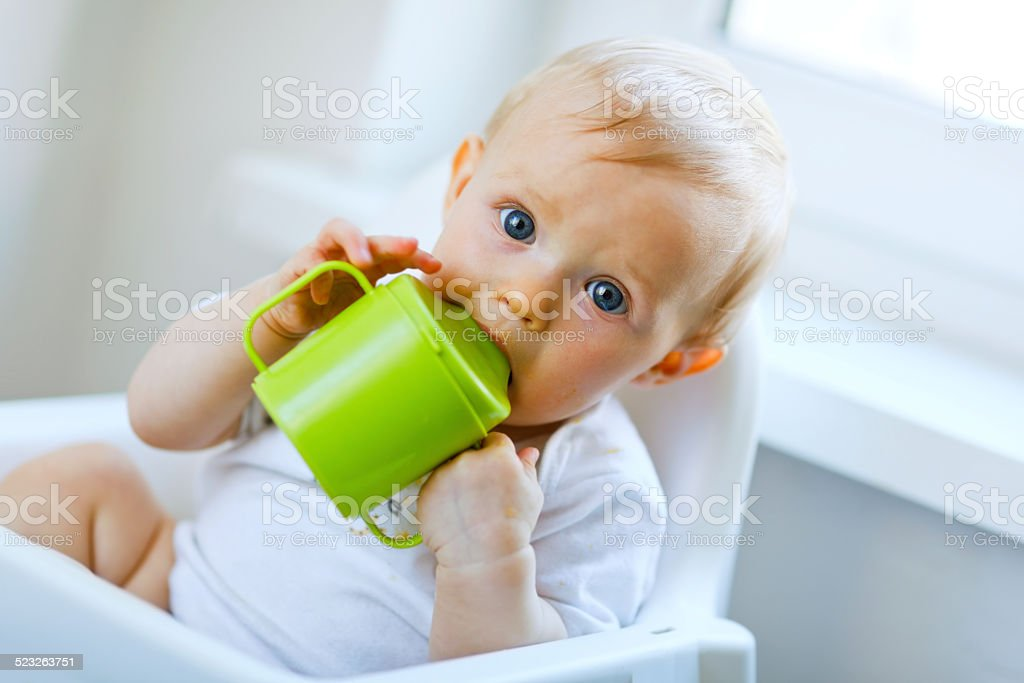 Lovely baby  sitting in chair and drinking from cup stock photo