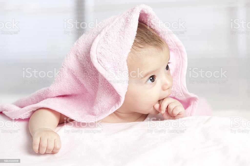 Lovely baby under pink towel. royalty-free stock photo