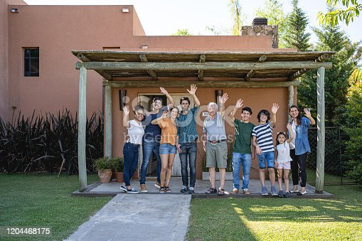 1196170672istockphoto Lovely big Latin family waving in front of their house 1204468175