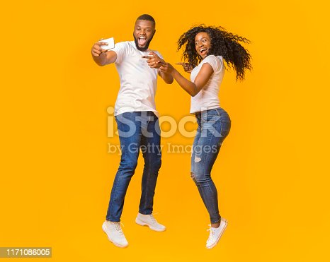 Smiling African American Couple Is Taking Selfie While Jumping, pointing at camera, yellow studio background