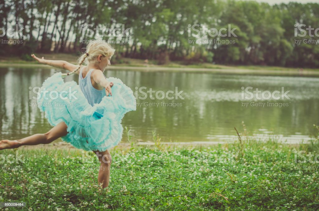 lovely blond girl in the meadow near the river stock photo