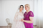 Millennial couple with kids and tattoos getting married. Here is the traditional wedding portrait of the bride after the ceremony with mother. Horizontal waist up outdoors shot with some copy space.