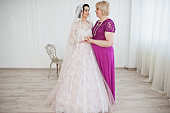Lovely bride in wedding gown posing with her mother in purple long dress. Black and white photo.