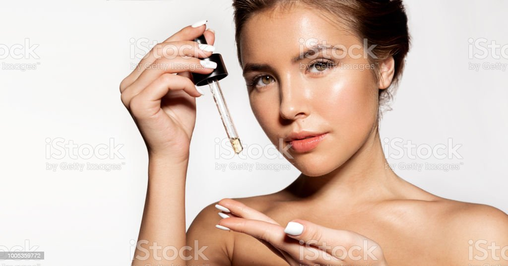 Lovely brunette with cosmetic oil in pipette royalty-free stock photo