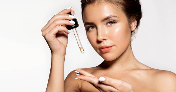 Lovely brunette with cosmetic oil in pipette stock photo