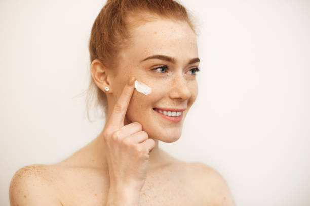 Lovely caucasian girl with red hair and freckles is smiling while using a cream on her face stock photo