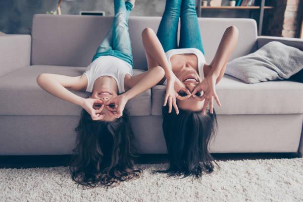 Belle mère heureuse joyeuse et espiègle petite fille avec les cheveux longs sont couché à l'envers sur un divan et faire des jumelles avec leurs doigts - Photo