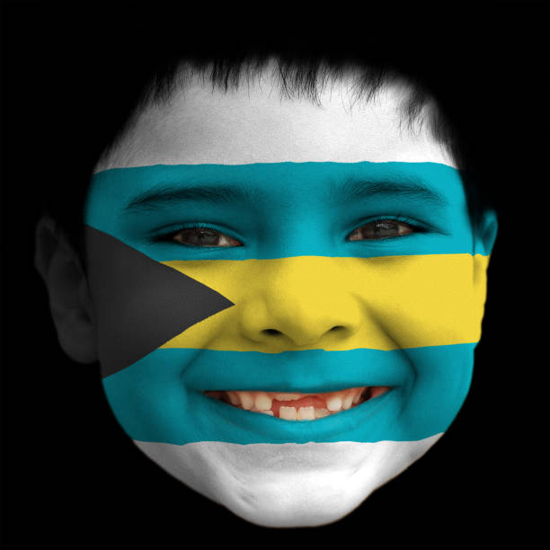 A lovely cheerful six year old boy smiling with broken incisors and half grown incisor teeth with Bahamas flag painted on his face stock photo