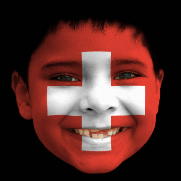 A lovely cheerful six year old boy smiling with broken incisors and half grown incisor teeth with Switzerland/ Swiss flag painted on his face stock photo