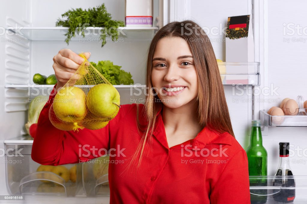 Lovely cheerful woman with pretty look holds fresh green apples, satisfied as they are her favourite fruits, going to make juice, poses near fridge with products. Female vegeterian with fruits stock photo