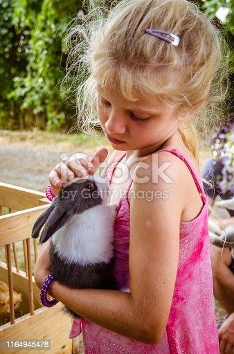 adorable little girl holding fluffy bunny