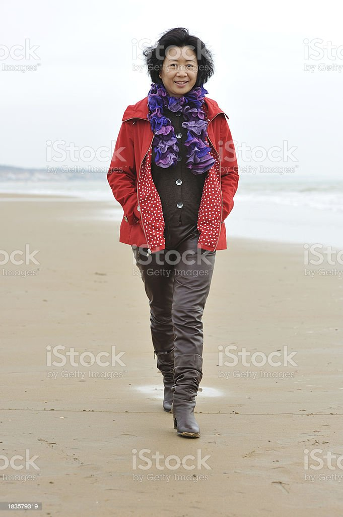 Lovely Chinese mature woman walking on the beach stock photo