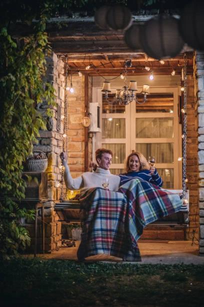 schönes paar weingenuss auf einer veranda-schaukel - veranda decke stock-fotos und bilder