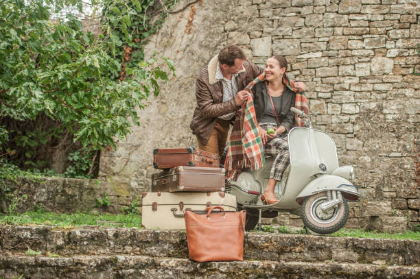 Lovely Couple Having Fun Riding Vintage Scooter in Old  Medieval Town Village of Grožnjan in Croatia stock photo