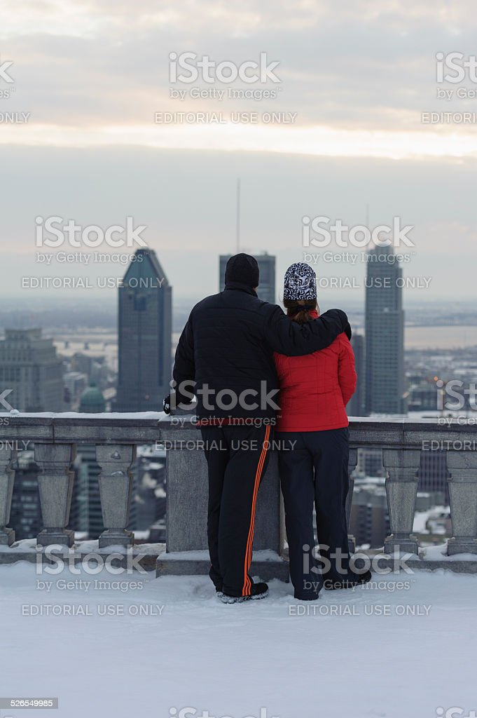 lovely couple looking at the city of Montreal during sunrise stock photo