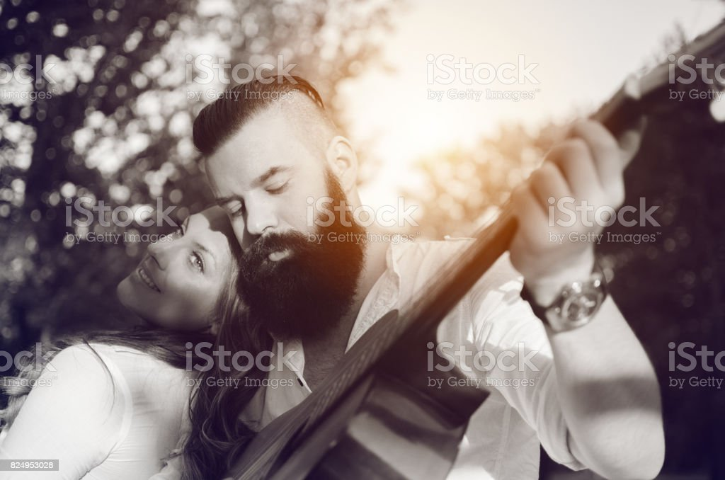 lovely couple relaxing with guitar outdoors stock photo
