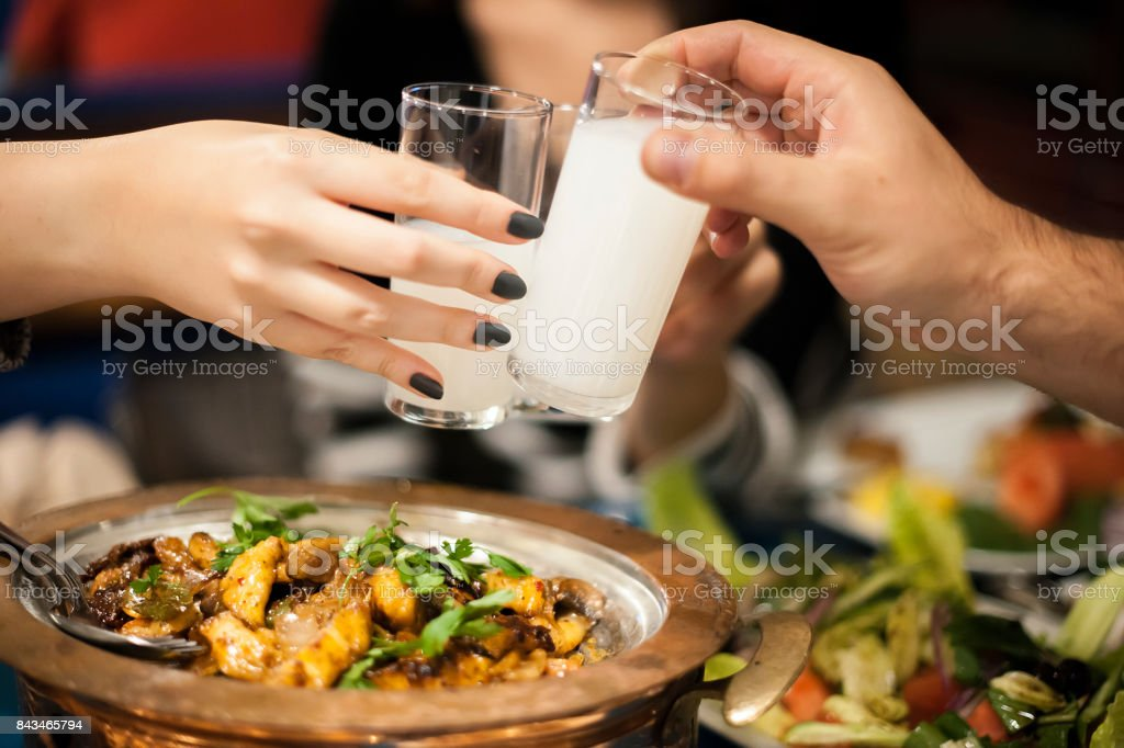 Lovely Couple Sitting, Drinking, Say Cheers and drinking Turkish Traditional Drink Raki, Ouzo stock photo
