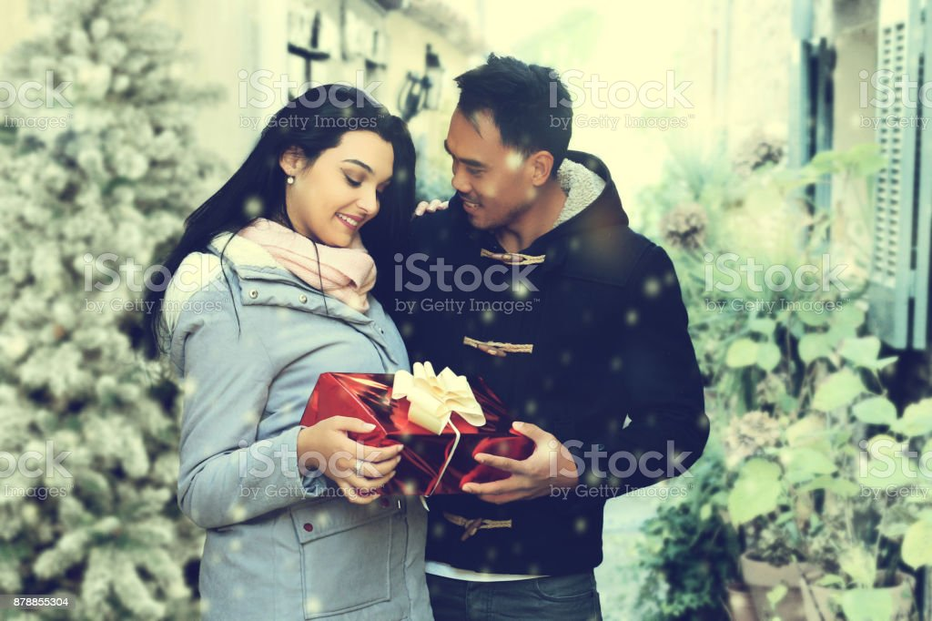 Lovely couple with a Christmas gift standing in the street stock photo