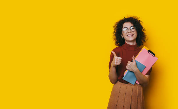 Lovely curly haired student holding some books is recommending something by posing on a yellow blank spaced background and showing the approbation sign Lovely curly haired student holding some books is recommending something by posing on a yellow blank spaced background and showing the approbation sign approbation stock pictures, royalty-free photos & images