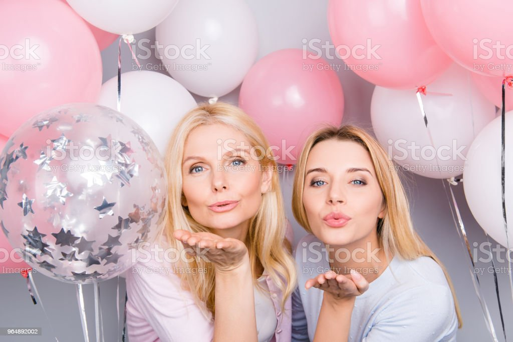 Lovely cute flirting tempting seductive sexy friendly mother and daughter sending kiss with pout lips and hand at camera having white pink decorations air balloons around isolated on grey background royalty-free stock photo