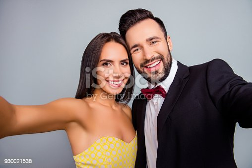 istock Lovely, cute, smiling, attractive, sexy couple, husband and wife in elegant outfit, tux, dress with beaming smiles making selfie together in two hands over grey background, 14 february 930021538