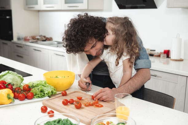 Lovely daughter enjoying food preparation together with her dad I love you, daddy. Pretty little girl is kissing her father cheek with gentleness. Man is smiling with happiness while cooking healthy dinner little girl kissing dad on cheek stock pictures, royalty-free photos & images