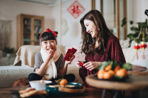 lovely daughter enjoying traditional snacks while helping her mother to prepare red envelops (lai see) at home for chinese new year - chinese new year stock pictures, royalty-free photos & images