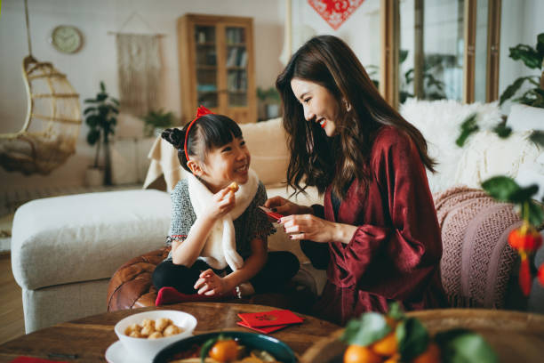 Lovely daughter enjoying traditional snacks while helping her mother to prepare red envelops (lai see) at home for Chinese New Year