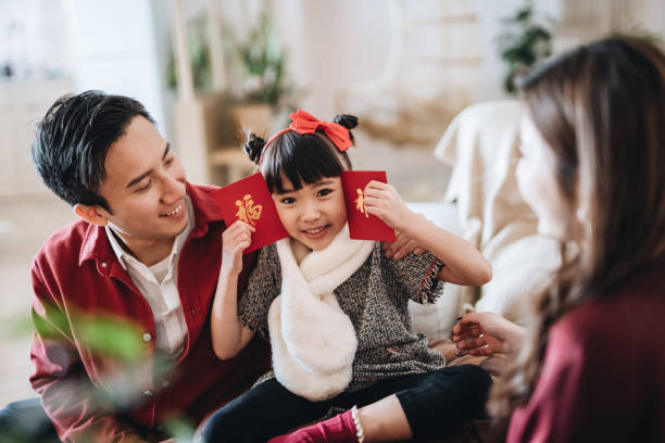lovely daughter happily received red envelops (lai see) from her parents in chinese new year - chinese new year stock pictures, royalty-free photos & images