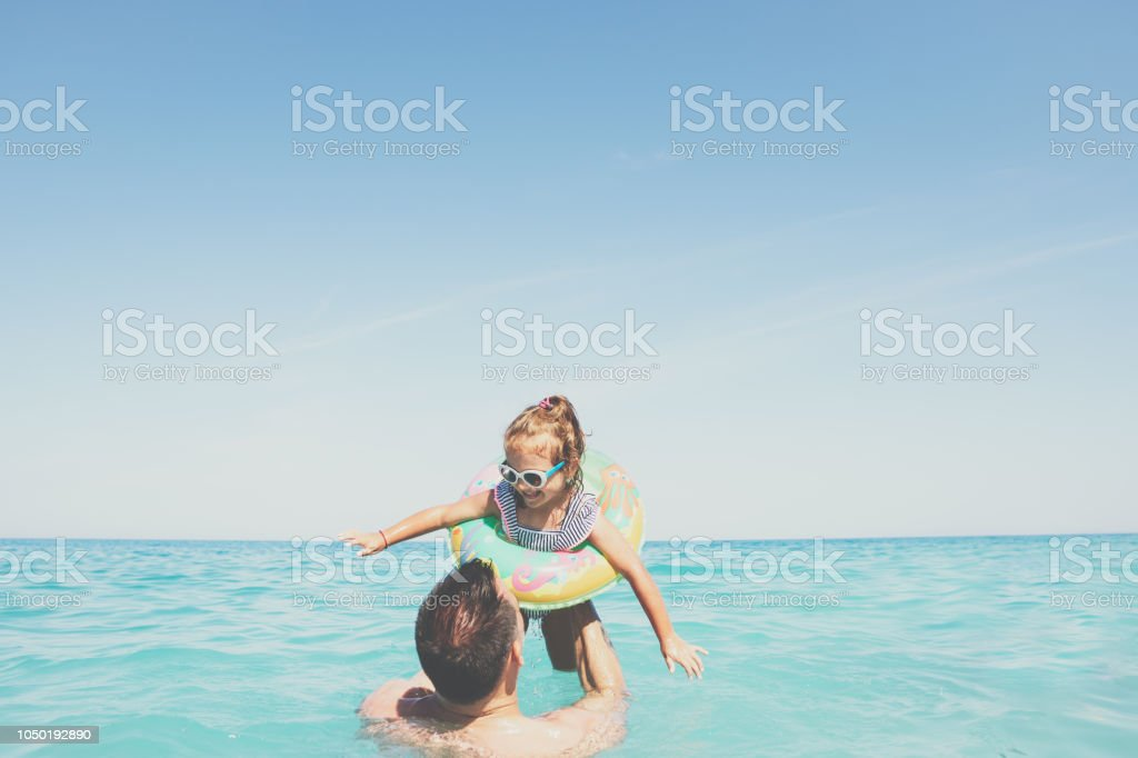 Lovely daughter playing at the beach with the dad stock photo