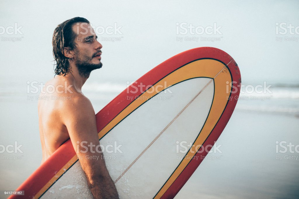 One man, handsome surfer holding surfboard on the beach.