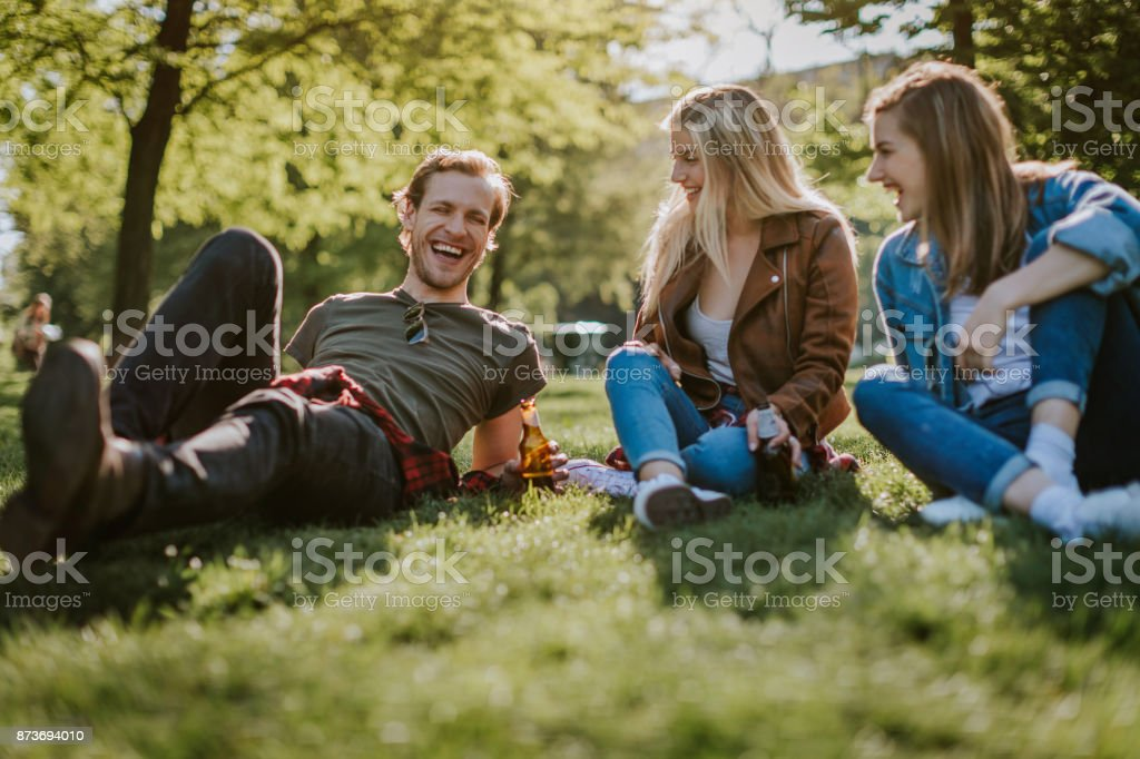 Friends in public park drinking cold beer