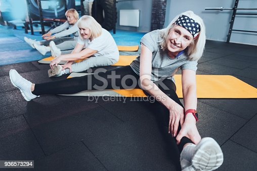 936573360 istock photo Lovely elderly woman stretching during training session 936573294