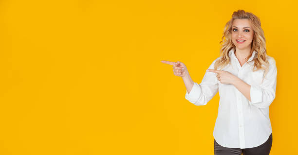 Lovely enthusiastic cute blond woman in a white shirt, pointing fingers to the left and smiling, stock photo