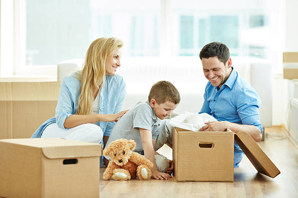 lovely family unpacking - happy mom packing some toys stock photos and pictures