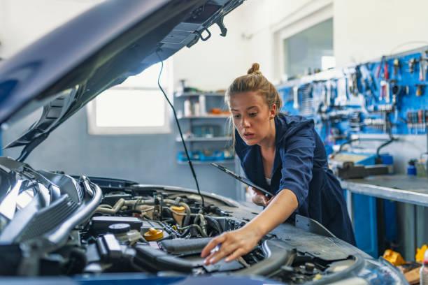 schöne weibliche automechanikerin, prüfung motor eines autos - autowerkstatt stock-fotos und bilder