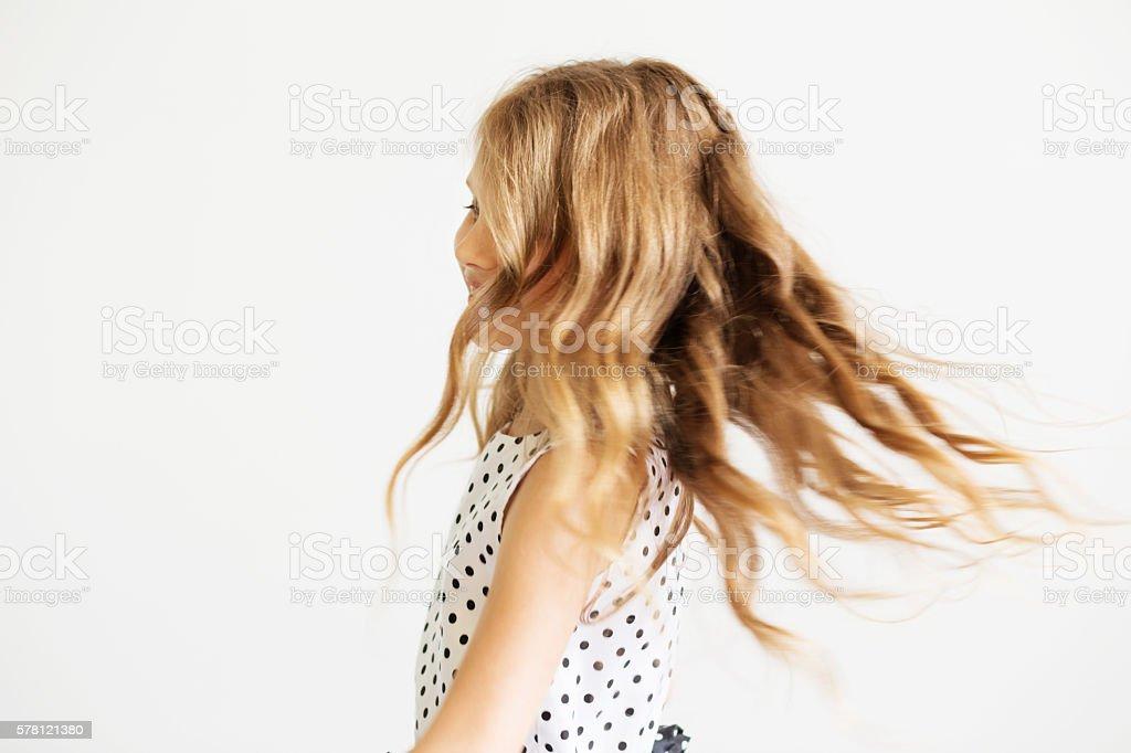 Lovely frisky little girl in a polka-dot dress stock photo