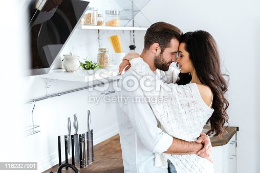 lovely gently couple embracing with closed eyes at kitchen