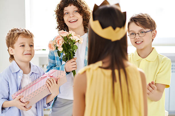 Lovely gift-givers Cheerful boys giving birthday gifts to female friend group of friends giving gifts to the birthday girl stock pictures, royalty-free photos & images