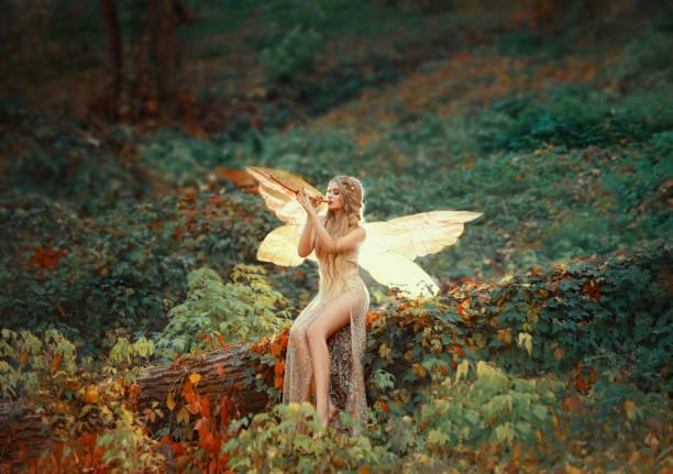 schöne mädchen druide mit blonden langen haaren, sitzt auf einen umgestürzten baum, gekleidet in eine wunderschöne beige kleid mit offenen sexy schlanke beine, umwandlung in einen lichten wald schmetterling auf ein hölzernes rohr allein blinkt - elfenkostüm damen stock-fotos und bilder