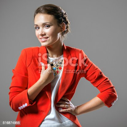Beautiful smiling young woman in red jacket standing on gray background
