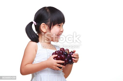 studio shoot of lovely asian girl holding grape