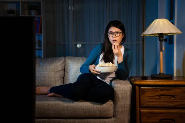 schöne mädchen popcorn schachtel halten und mit blick auf tv - mädchen night snacks stock-fotos und bilder